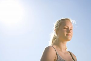 Head and shoulders of a blonde lady with her eyes closed and her back to the sun, with a clear blue sky